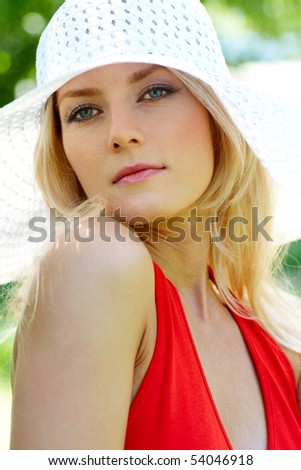 Vertical image of pretty young lady in elegant hat looking aside - stock photo