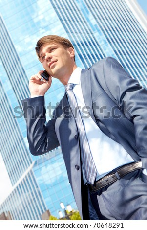 Vertical image of successful boss calling by mobile near a modern building - stock photo