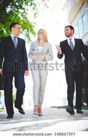 Vertical image of three business partners talking while walking down modern street  - stock photo