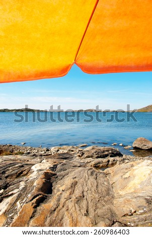 Vertical Image With Swedish Coastline Bohuslan Archipelago Swedish West Coast With Rocks And Cliffs Beautiful Beach With Orange Parasol With Ocean And Sea Sunny Weather With Blue Sky - stock photo