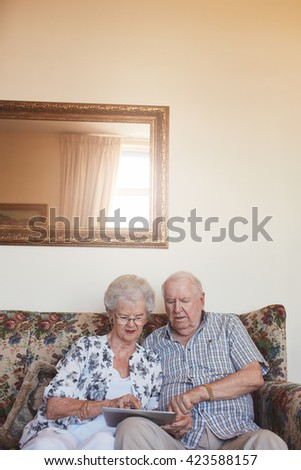 Vertical indoor shot of retired couple at home using digital tablet. Senior caucasian man and woman sitting together on sofa at home with a touch screen computer. - stock photo