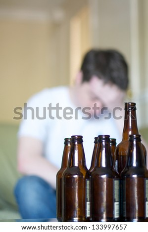 Vertical, man holding his head up with empty beer bottles - stock photo