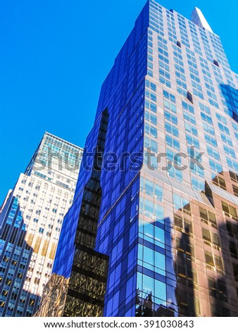 Vertical of modern shiny blue facade of high rise buildings in Manhattan, New York city, USA. - stock photo