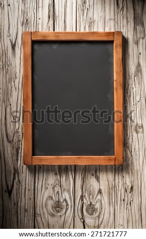 vertical old chalkboard on very aged wooden wall - stock photo