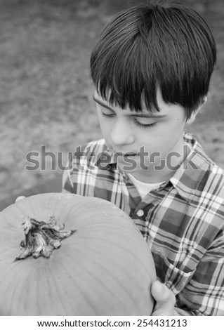 vertical orientation black and white image of an attractive teenage boy with autism and down's syndrome holding a large pumpkin / Pumpkin Harvest - stock photo