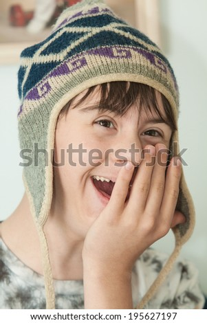 vertical orientation close up of a teenage boy with autism and down's syndrome, wearing a winter wool hat, with his hand on his face, looking surprised and happy / Surprised Teenage Boy - stock photo