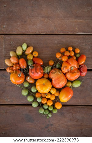 vertical orientation close up of a variety of colorful tomatoes in the shape of a heart, on a neutral wooden background / Healthy Heart of Tomatoes - stock photo