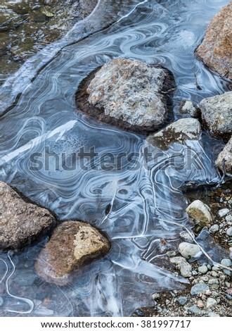vertical orientation color image of water currents frozen around rocks in a creek in winter time / Ripples Frozen in Time - stock photo