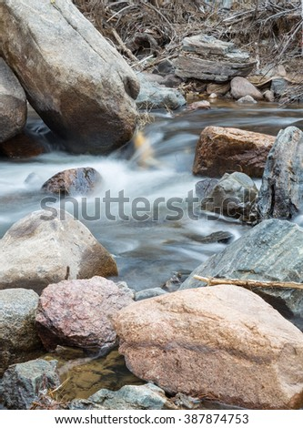 vertical orientation color image, taken with a very slow shutter speed to show the movement of water in a creek through a rocky landscape / Beautiful Rocky Mountain Creek - stock photo