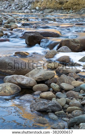 vertical orientation color image, taken with very slow shutter speed to show water flowing over rocks in a creek in Colorado / Tranquil Flowing Water in Winter - stock photo