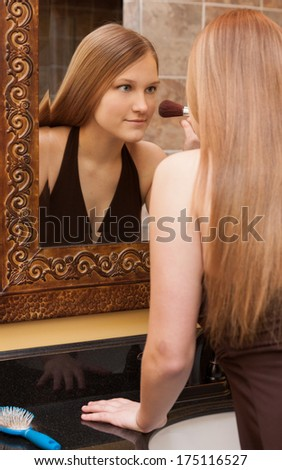 vertical orientation of a lovely teenage girl with long hair applying makeup with a brush as she looks into the mirror / Brushing up on Beauty - stock photo