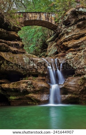 Vertical orientation of a peaceful waterfall with a stone footbridge crossing the gorge. Hocking Hills State Park. Logan, Ohio. - stock photo