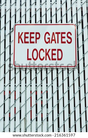 vertical orientation of a white fence with a generic sign that states KEEP GATES LOCKED and copy space / Keep Gates Locked Sign - Vertical - stock photo