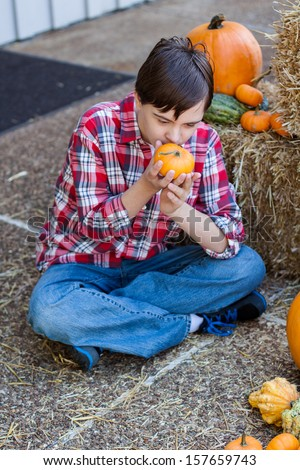 vertical orientation of boy with autism and down's syndrome seated outside on a sunny day with hay and harvest vegetables around him and copy space / Boy with Autism Inspecting Pumpkin - stock photo
