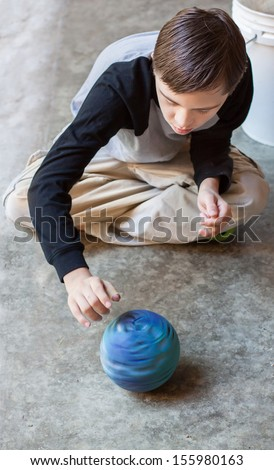 vertical orientation of boy with autism and down's syndrome sitting cross legged on a cement floor spinning a bright blue ball / Boy with Autism spins a Ball - stock photo