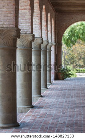vertical orientation of long outdoor hallway with majestic columns on one side and copy space / Beautiful Columns and Brick Walkway - stock photo