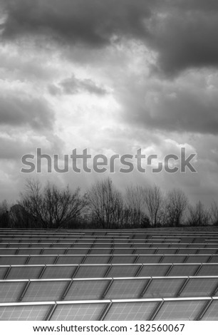 vertical orientation of solar panels in a field on a cloudy day in Black and White with High Dynamic Range (HDR) detail and copy space / Solar Panels on a Cloudy Day - stock photo