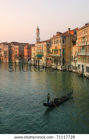 Vertical oriented image of gondola sailing on Grand Canal along old multicolored houses in Venice, Italy. - stock photo