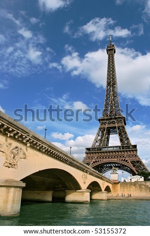 Vertical oriented photo of Eiffel Tower and fragment of bridge over the Seine River in Paris, France. - stock photo