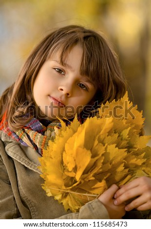 vertical photo,  beautiful little girl hold many yellow leaf, autumnal portrait - stock photo