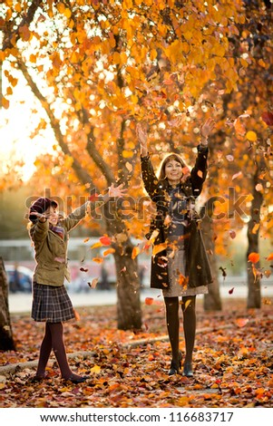 Vertical photo,  happy beautiful little girl with mather throw up  autumnal leafage, in park. Focus on little girl. - stock photo