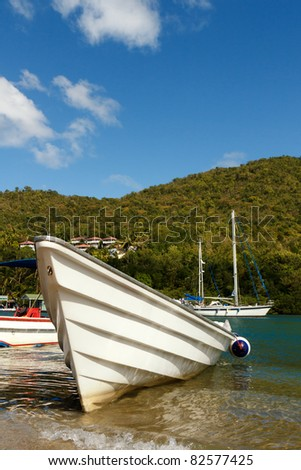 Vertical photo of a white fishing boat on Marigot Bay in the Caribbean island of St Lucia - stock photo