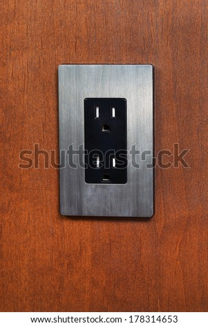 Vertical photo of an electrical outlet and face plate on cherry wood wall  - stock photo