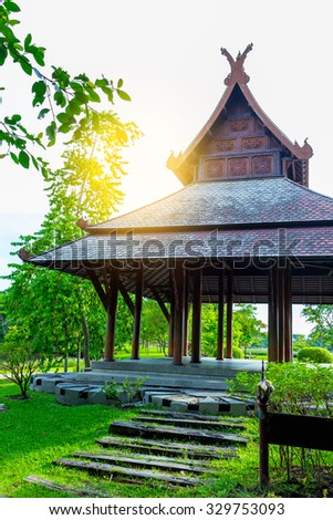 vertical photo of big asian country style pavilion & sunset in beautiful garden - stock photo