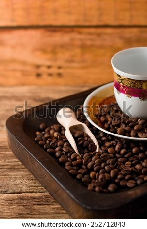 Vertical photo of coffee beans in dark wooden tray with coffee cup, plate and wooden spoon, everything placed on old worn board from wood - stock photo