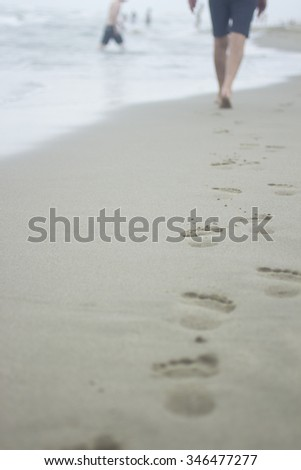 Vertical photo of legs of man wearing swimming shorts and footprints on sand of beach on grey cold day with sea and bathers defocused in background. Taken in Viareggio in Tuscany Italy  - stock photo
