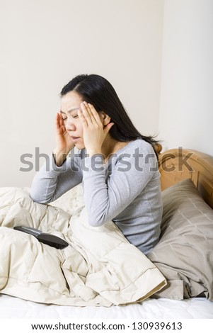 Vertical photo of mature woman, holding her head with both hands, while alarm clock is lying in bed - stock photo