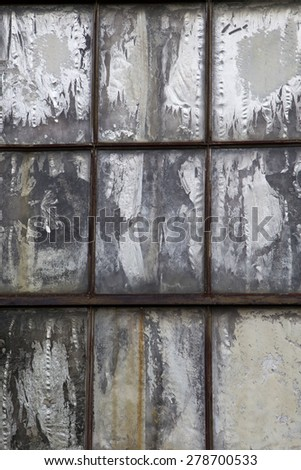 Vertical photo of old weathered rusted window boarded up with chipped and cracked grey panel - stock photo