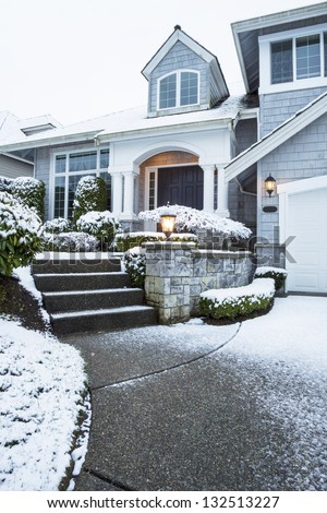 Vertical photo of side walk leading to suburban home with snow on ground - stock photo