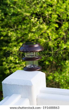 Vertical photo of solar lamp, during day light, on deck post with green trees in background  - stock photo