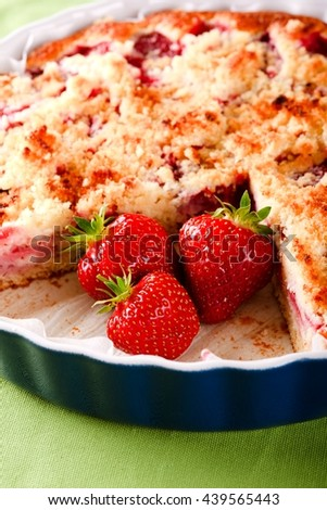 Vertical photo of three red juicy strawberries on position of cut off portion from sweet fruit strawberry pie in blue ovenproof dish. Fruit cake on green towel. Fruit with pie in bowl. - stock photo