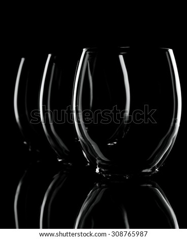 Vertical photo of tree glasses in a row with small overlapping. Each glass ia smaller that the previous one. Only contours are visible with nice reflection on the bottom. Background is black. - stock photo