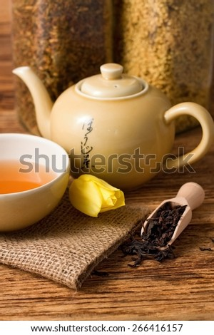 Vertical photo of Tulip bloom next to oriental tea set on jute cloth and wooden spoon full of tea dry leafs plus kettle and two jars with herbs all on wooden table. - stock photo