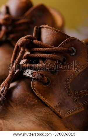Vertical photo with detail of very old and worn shoelaces which are placed on old leather boots. - stock photo