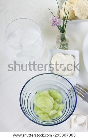 Vertical photo with top view on blue glass bowl with cucumber salad. Fork, glass with ice cold drink, salt and flower plus few pieces of vegetable are around on white cloth. - stock photo