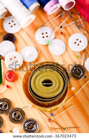 Vertical photo with top view on tailoring accessories placed on light wooden color like color pins, tape measure, several knobs, needles and sewing.  - stock photo
