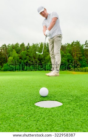 Vertical picture man playing golf on a green field - stock photo