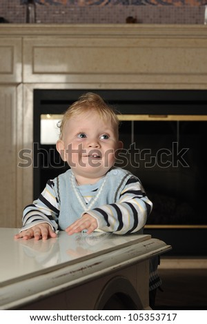 Vertical portrait of a baby boy in a striped sweater and a vest standing next to a coffee table looking up smiling - stock photo