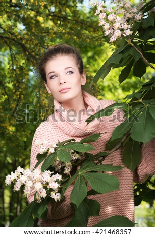 Vertical portrait of a beautiful young woman in a pink sweater in a lush garden. A woman peeks out from behind a blossoming tree branch - stock photo