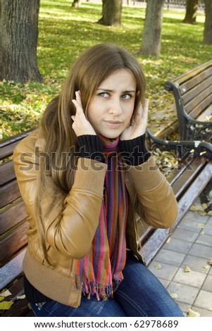 Vertical portrait of a beautiful young woman sitting on a bench in the park around a lot of yellow, red green leaves. Girl puts his hand over his ears so as not to hear the street noise - stock photo