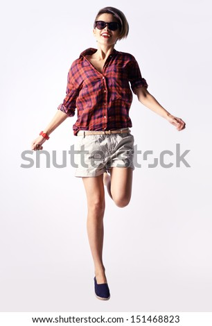 Vertical portrait of a carefree girl captured in a jump - stock photo