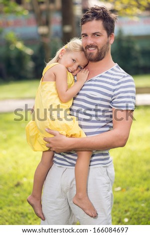 Vertical portrait of a father holding his daughter in hands with care and tenderness  - stock photo