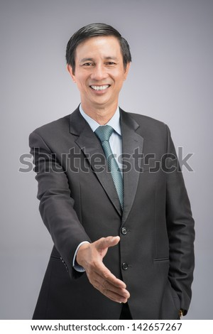 Vertical portrait of a gesturing businessman on a grey background - stock photo
