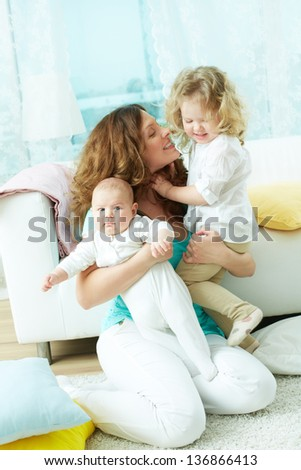 Vertical portrait of a happy family of three at home - stock photo