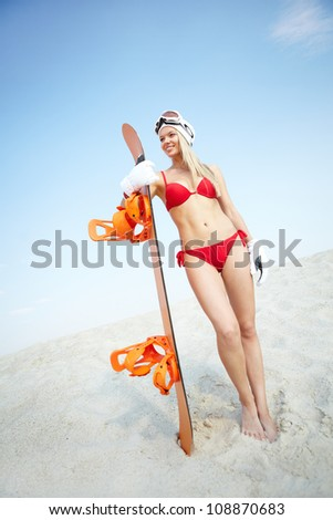 Vertical portrait of a lovely girl standing on sand with snowboard in her hands - stock photo