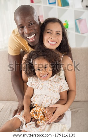 Vertical portrait of a mixed cheerful family posing at camera  - stock photo